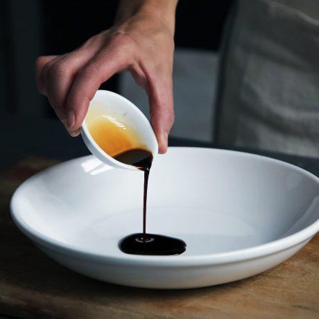 Balsamicocreme wird von einer Schale in einen Teller umgeschüttet